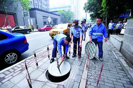 昨日,人和街,维修人员接到指令后对问题窨井盖进行更换。记者 张路桥 摄